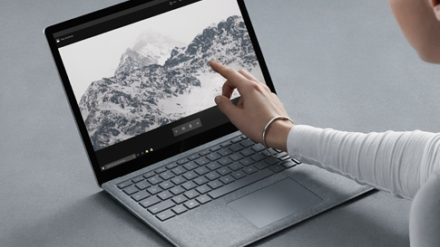 En kvinna tar på skärmen av en platinafärgad Surface Laptop.