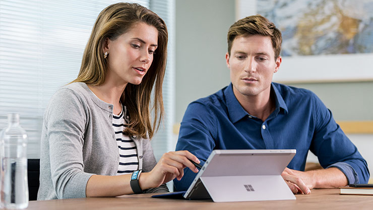 Två kvinnor som tittar på en Surface Book.