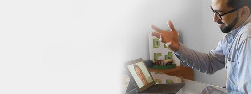 ผู้ชายคนหนึ่งกำลังนั่งประชุมทางวิดีโอบนโต๊ะผ่านแท็บเล็ตโดยใช้ Office 365