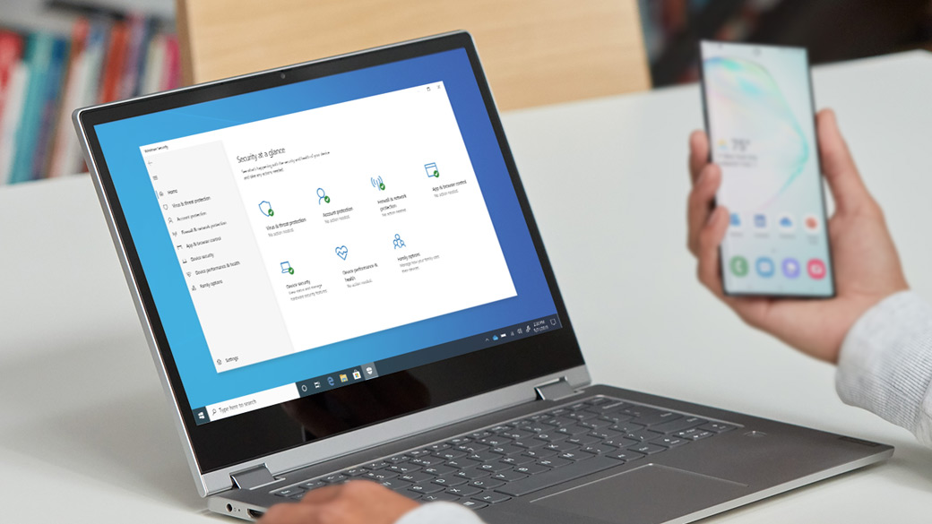 คนคนหนึ่งดูโทรศัพท์มือถือขณะที่แล็ปท็อป Windows 10 แสดงฟีเจอร์ความปลอดภัย
