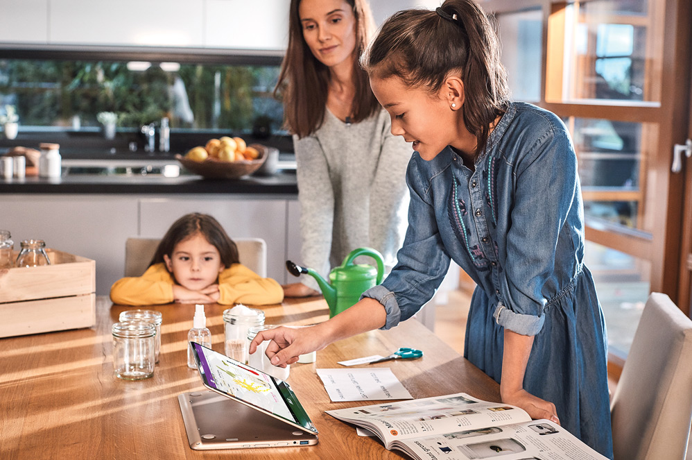 ครอบครัวหนึ่งอยู่ในห้องครัว พร้อมคอมพิวเตอร์ Windows 10 แบบทูอินวันที่มีจอสัมผัส