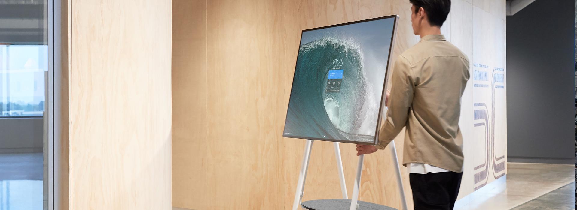 ผู้ชายคนหนึ่งขนย้าย Surface Hub 2S บนขาตั้งเคลื่อนที่แบบมีล้อหมุน