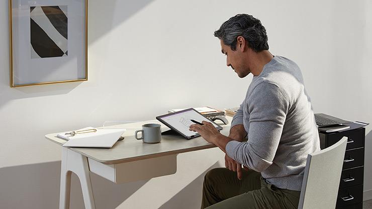 ผู้ชายคนหนึ่งใช้หมึกด้วยปากกา Surface บน Surface Pro