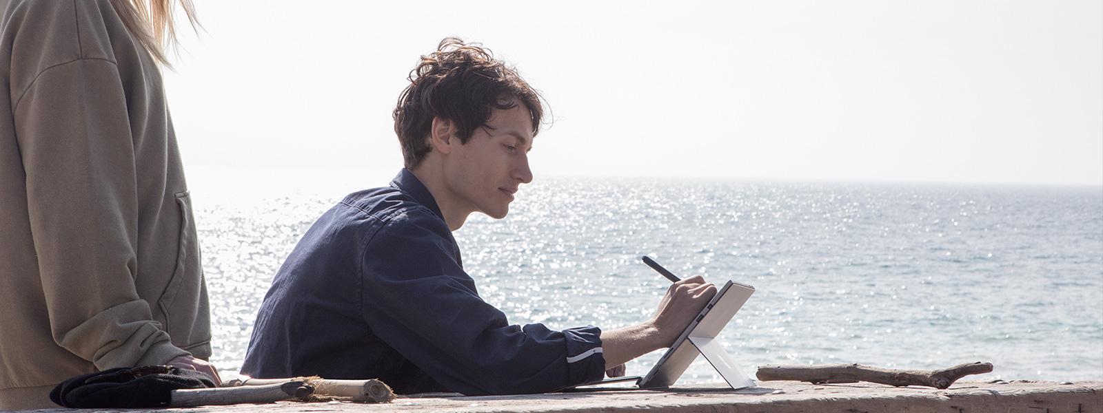 ผู้ชายกำลังใช้ Surface Pro อยู่ภายนอกอาคาร