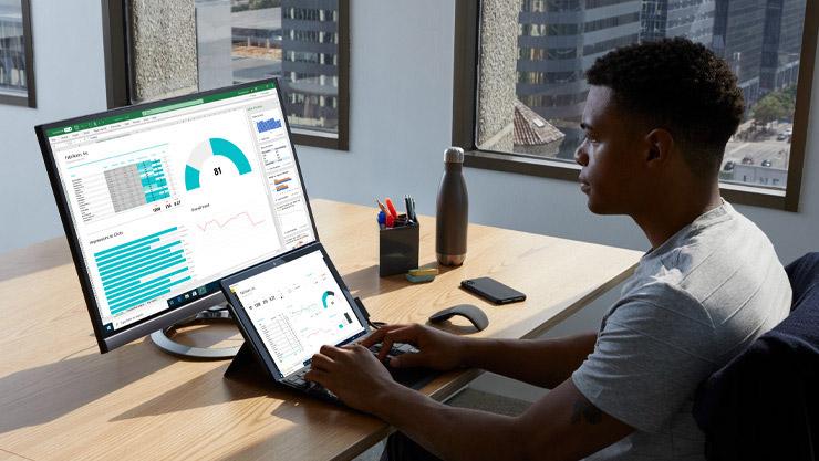 ผู้ชายคนหนึ่งทำงานด้วยอุปกรณ์ Surface ที่โต๊ะทำงาน