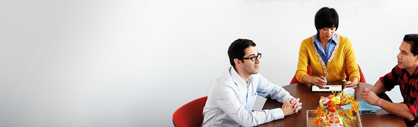 คน 3 คนนั่งประชุมกันอยู่ที่โต๊ะกำลังใช้ Office 365 Nonprofit บนแท็บเล็ตและโทรศัพท์
