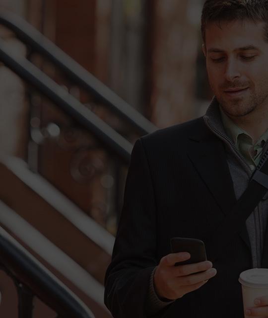 ผู้ชายถือสมาร์ทโฟนกำลังใช้ Office 365 Enterprise E1