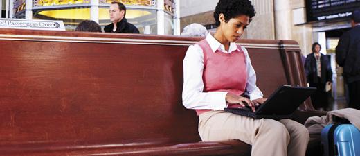 ผู้หญิงคนหนึ่งในสถานีรถไฟกำลังทำงานบนแล็ปท็อป กำลังเรียนรู้เกี่ยวกับฟีเจอร์และราคาของ Exchange Online Protection