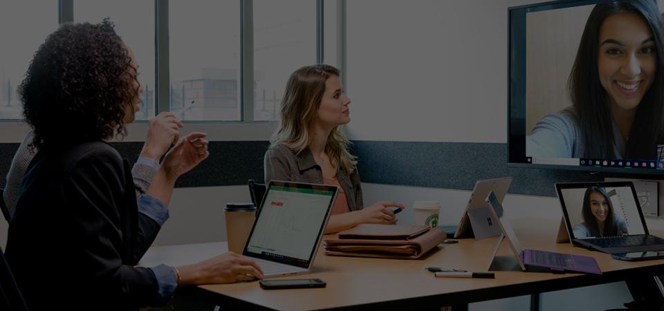 รูปถ่ายของผู้คนในห้องประชุมที่ใช้อุปกรณ์ที่เชื่อมต่อ Teams