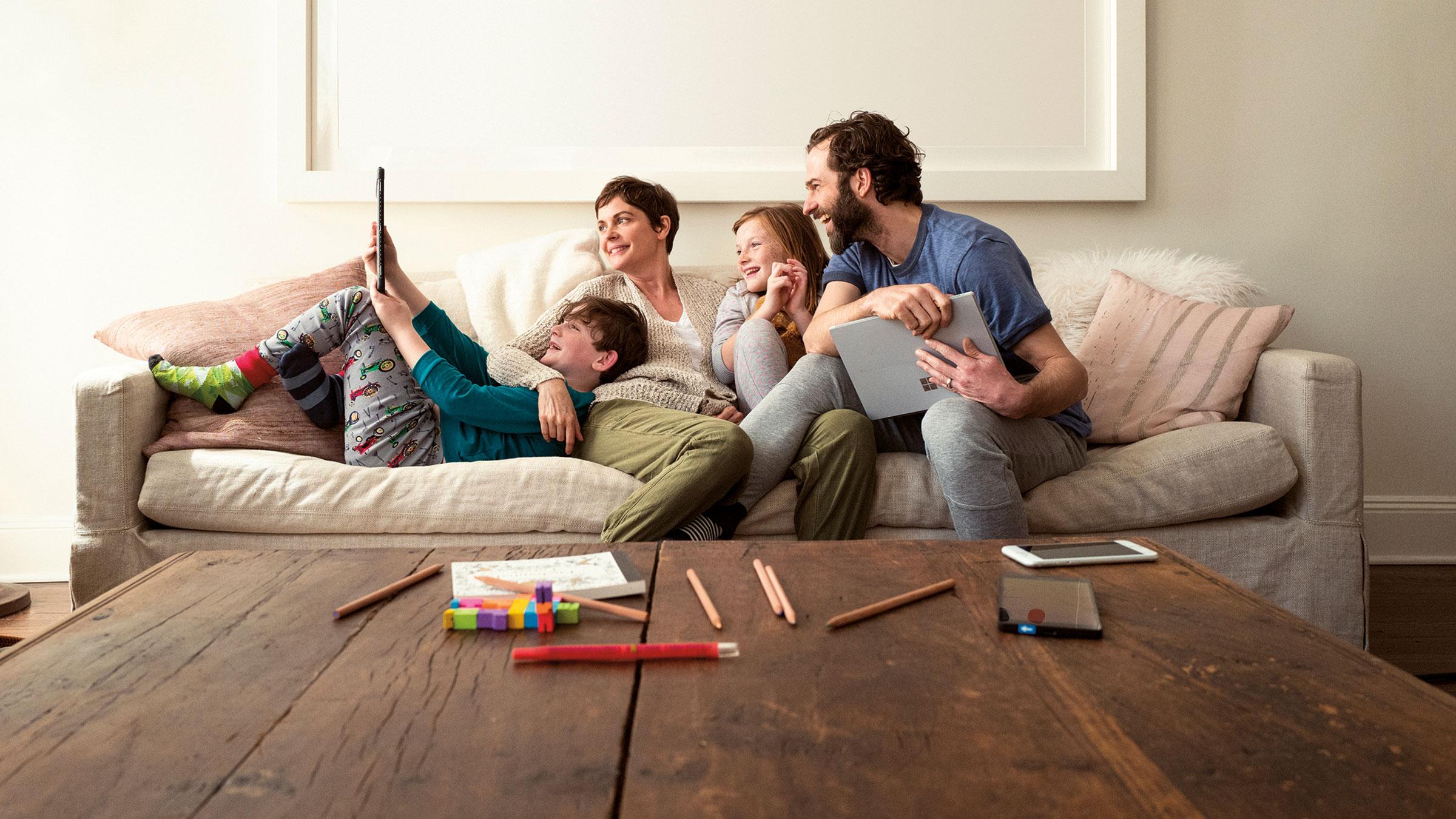 ครอบครัวนั่งอยู่บนโซฟาและดูอุปกรณ์ Microsoft Surface Pro
