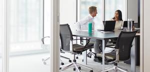 ผู้ชายและผู้หญิงนั่งอยู่ที่โต๊ะประชุมกำลังใช้ Office 365 Enterprise E3 บนแล็ปท็อป