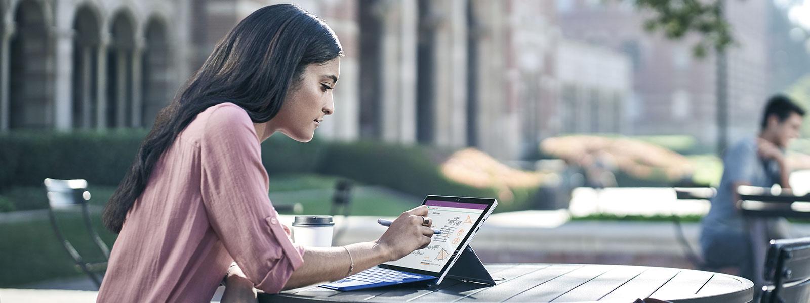 ผู้หญิงกำลังใช้ปากกา Surface วาดบนหน้าจอ Surface Studio ขณะจีบนิ้วด้วยมืออีกข้างเพื่อย่อหรือขยายหน้าจอ