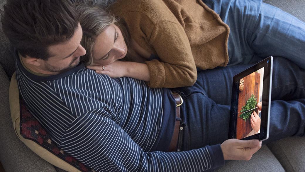 ชายหญิงกำลังนั่งพักผ่อนด้วยกันขณะสื่อสารกับ Surface Pro