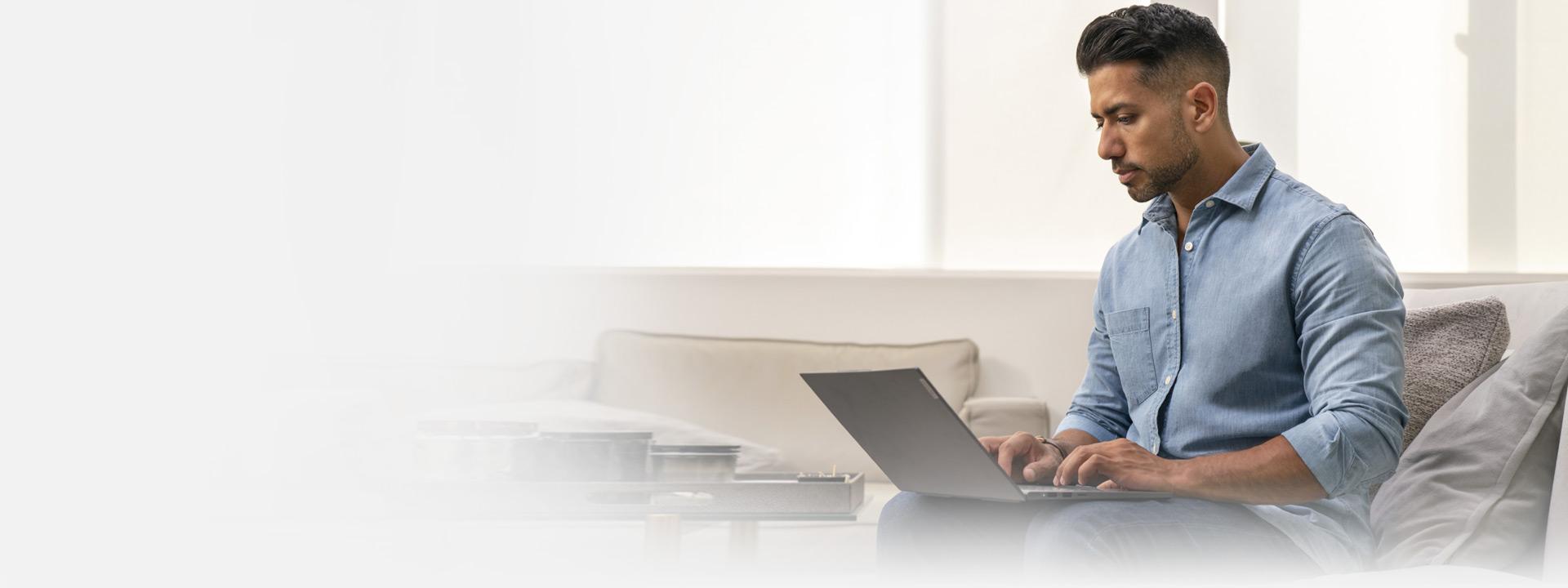 Adam kanepede otururken dizüstü bilgisayarını kullanıyor
