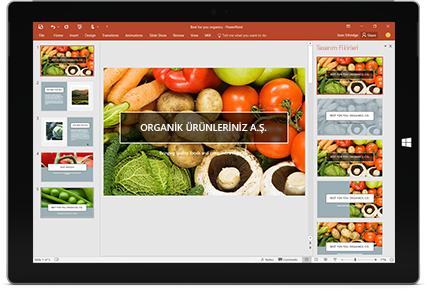PowerPoint sunu slaydı içinde Tasarımcı özelliğinin göründüğü bir tablet.