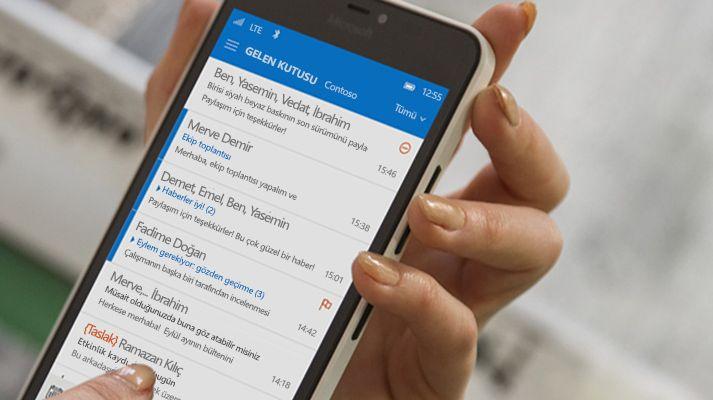 Akıllı telefonda Office 365 e-posta listesindeki bir iletiye dokunan el.
