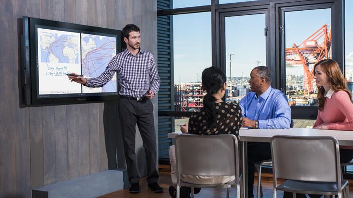 Жінка та двоє чоловіків сидять у конференц-залі, одна людина проводить презентацію