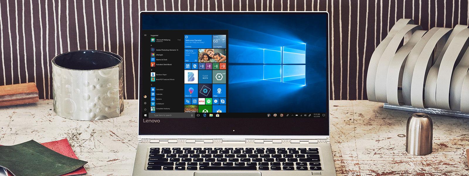 Máy tính xách tay đặt trên bàn đang hiển thị màn hình bắt đầu của Windows 10