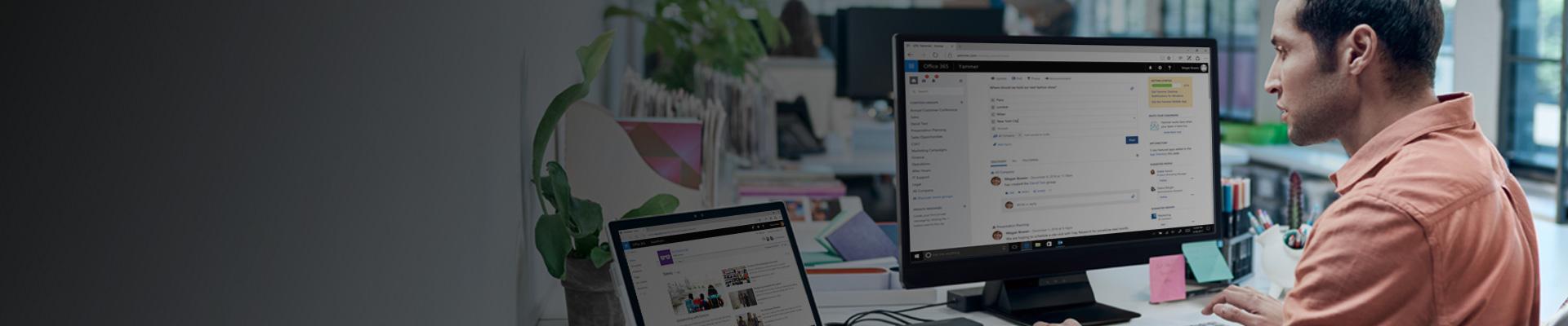 Một người đàn ông đang nhìn vào màn hình máy tính chạy SharePoint, với Yammer được hiển thị trong nền trên một màn hình khác