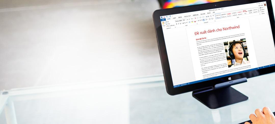Một nhân viên đang gõ bàn phím, trước mặt là tài liệu Word trên màn hình.