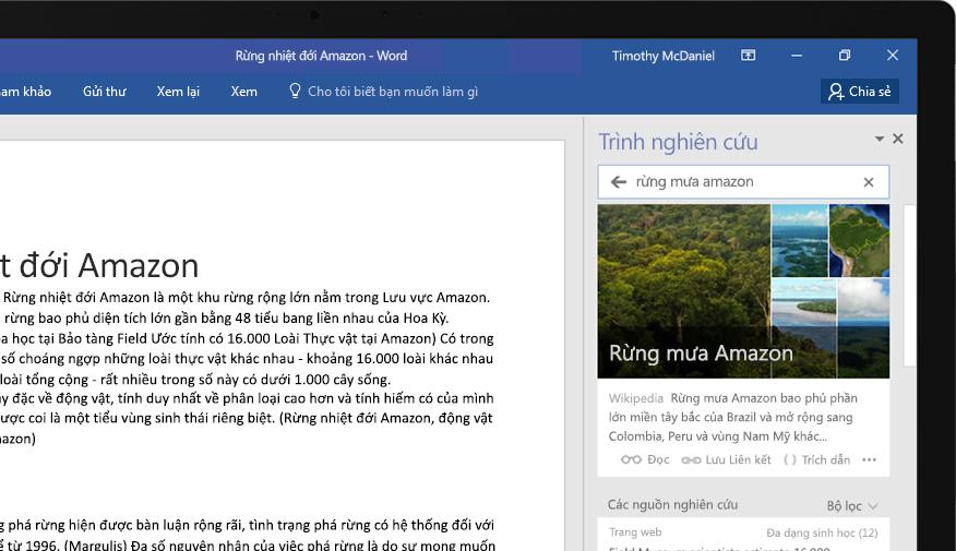 Máy tính xách tay hiển thị một tài liệu Word và hình ảnh cận cảnh tính năng Trình nghiên cứu với một bài viết về rừng mưa nhiệt đới Amazon