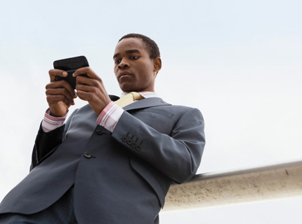 Một người đang làm việc trên điện thoại của mình bên ngoài văn phòng, bằng cách dùng Office Professional Plus 2013