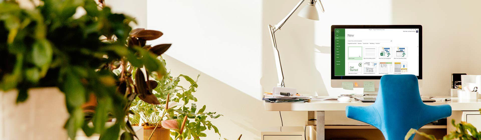 Một chiếc bàn với màn hình máy tính hiển thị cửa sổ Dự án Mới trong Microsoft Project.