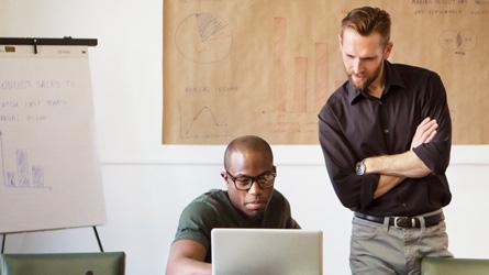 Hai người đàn ông trong văn phòng đang nhìn vào màn hình máy tính xách tay và đọc bài viết về chi phí và thách thức trong Khám phá Điện tử