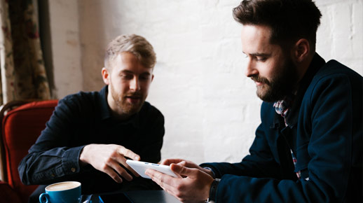 Hai người đàn ông đang nhìn vào một chiếc điện thoại