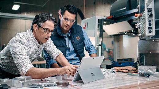 Hai người đàn ông làm việc trên một chiếc Surface