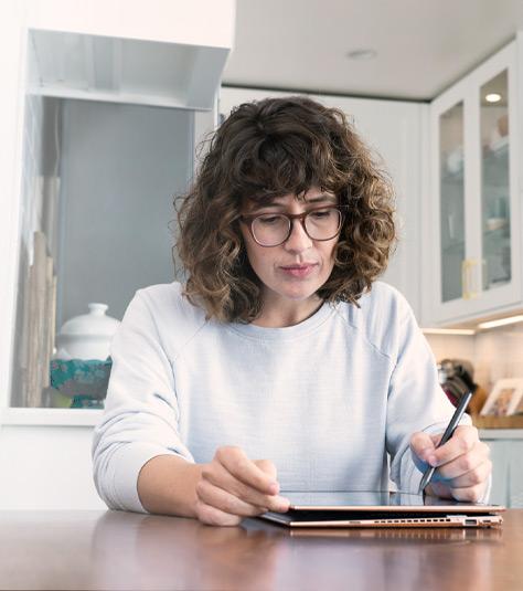 一位女士使用數字觸控筆在平板電腦上繪制