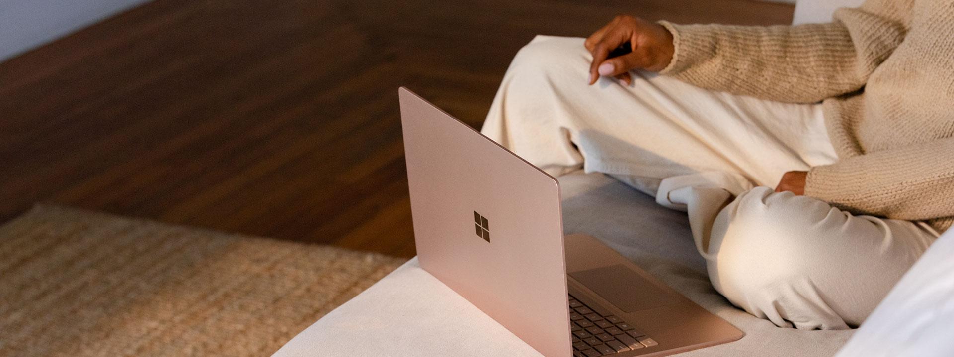 一位女性坐在沙发上,面前放着 Surface Laptop 3