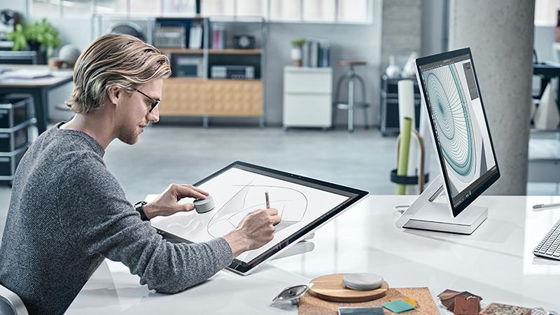 在现代办公环境中,一个男人边在 Surface Studio 屏幕上绘画边使用 Dial,面对着另一台 Surface Studio。