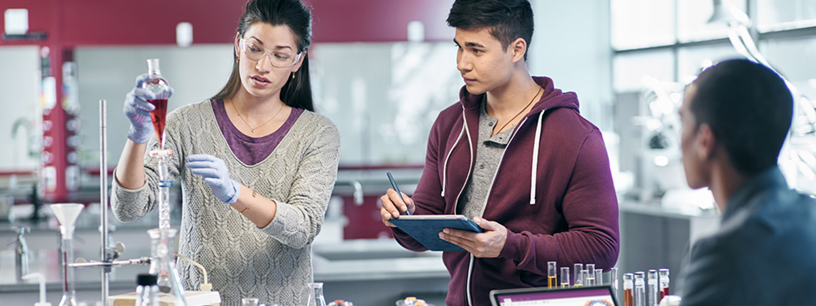 三个学生在化学实验室中,一人使用平板模式的 Surface Pro 4,一人使用笔记本模式的 Surface Pro 4。