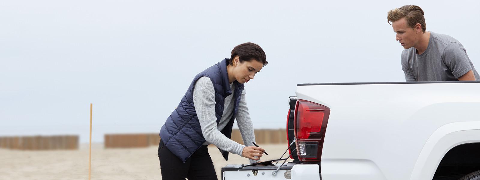 一名男子和一名女子站在一辆敞篷小货车旁边操作 Surface Pro X