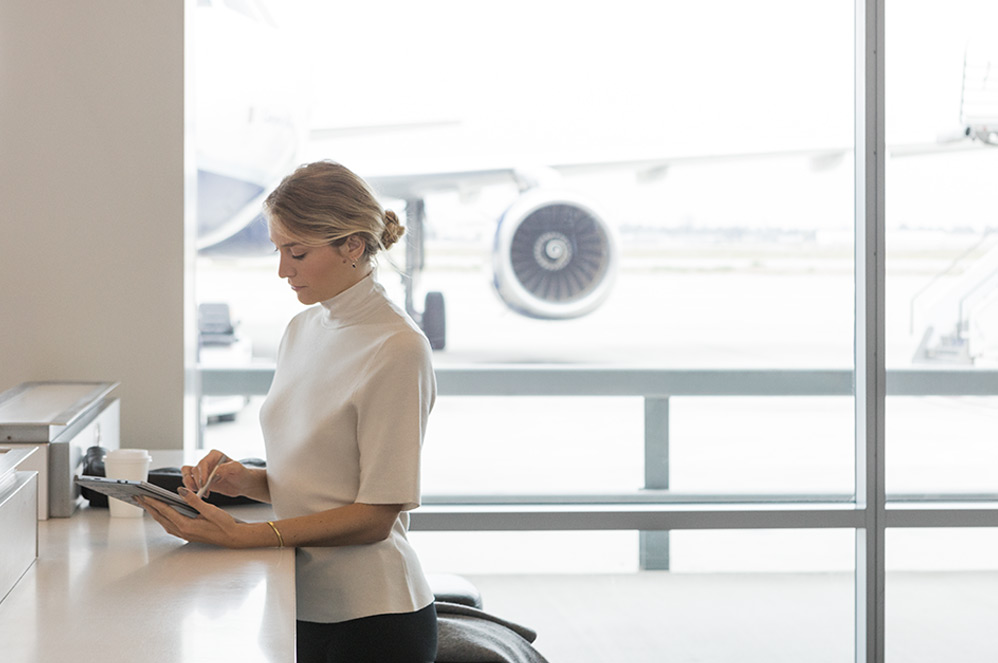一位女士在机场通过 Surface 触控笔使用平板模式下的 LTE Advanced 版 Surface Pro(5 代)工作。