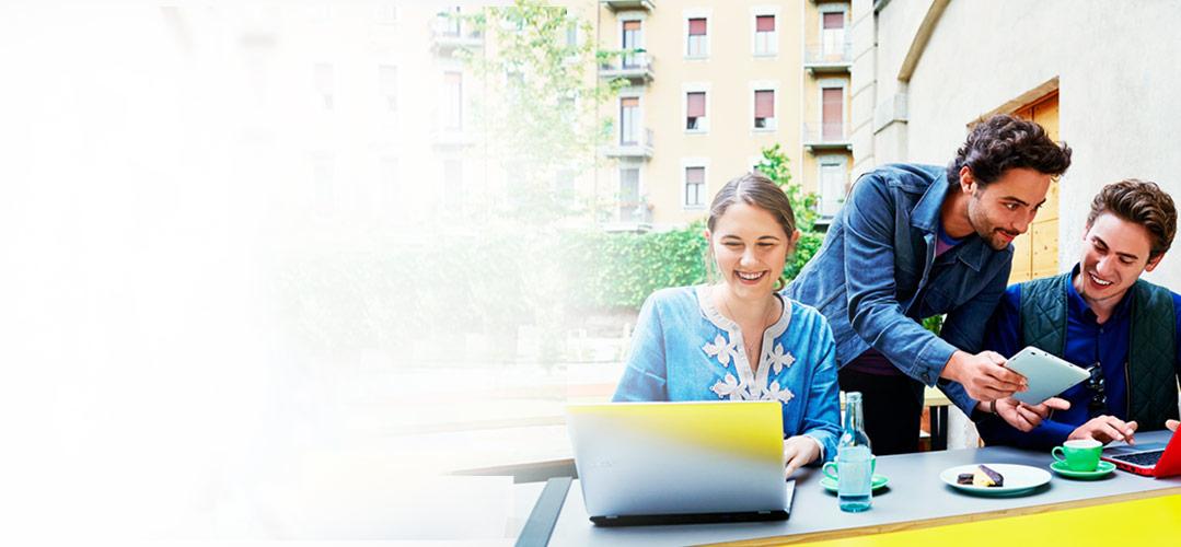 一位女士和两位男士在户外咖啡馆中使用笔记本电脑和平板电脑一起工作。