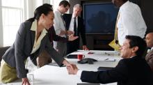 两人隔着桌子握手,了解 Office 365 如何提供更强的隐私、安全性和合规性