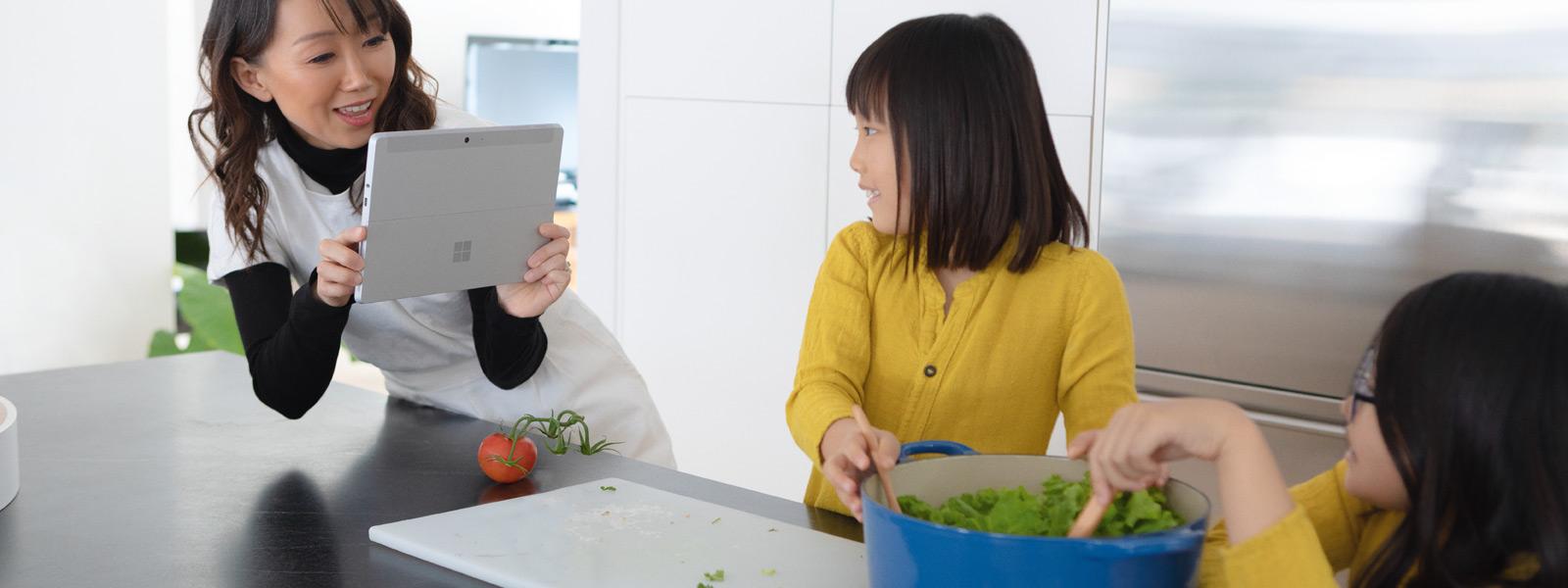 一位女士在用 Surface Go 给孩子拍照