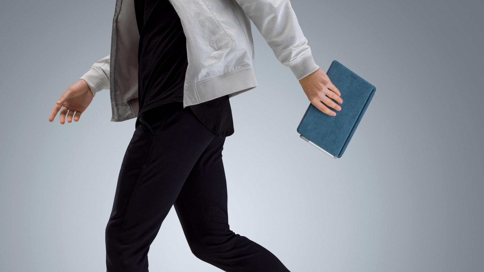 一位行走的男士带着配备蓝色 Surface Go Signature Type Cover 的 Surface Go