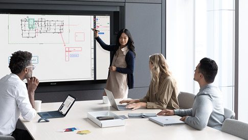 在工作会议中,女人指着 Surface Hub 上的内容