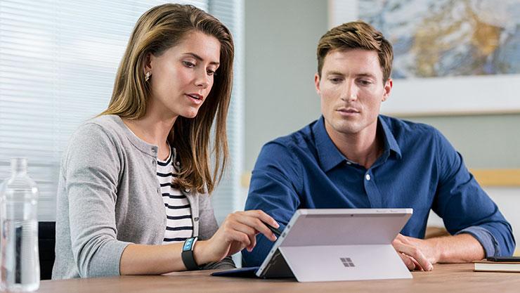 两个女人注视着 Surface Book
