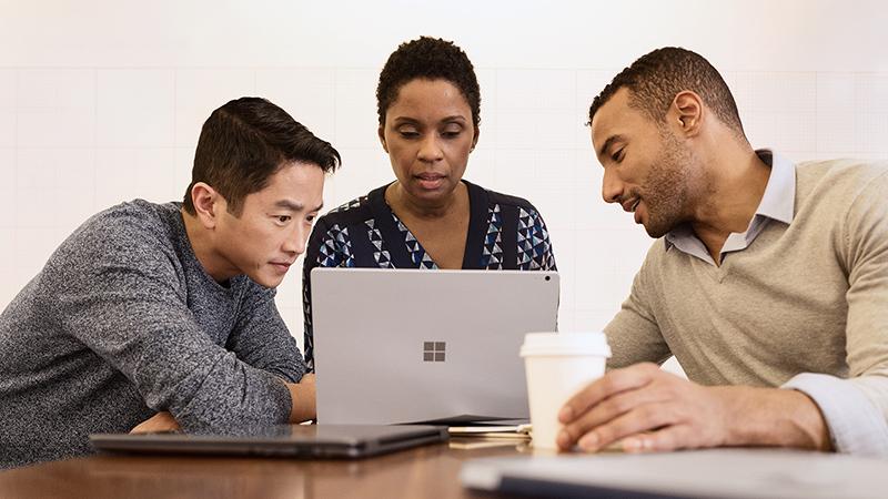 三个人正在看着一台 Windows 笔记本电脑