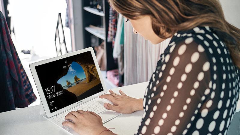 一位女士正坐在桌边使用附带键盘在平板电脑上打字