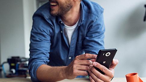 一位男士正看着一台 Windows 10 手机
