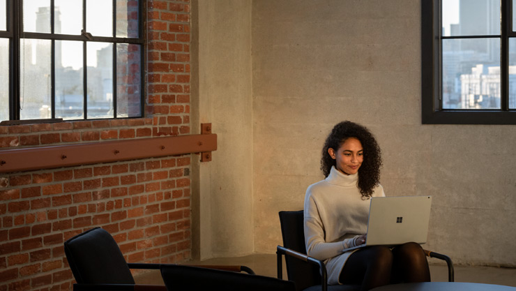 女人在家中,使用腿上的 Surface Laptop 工作
