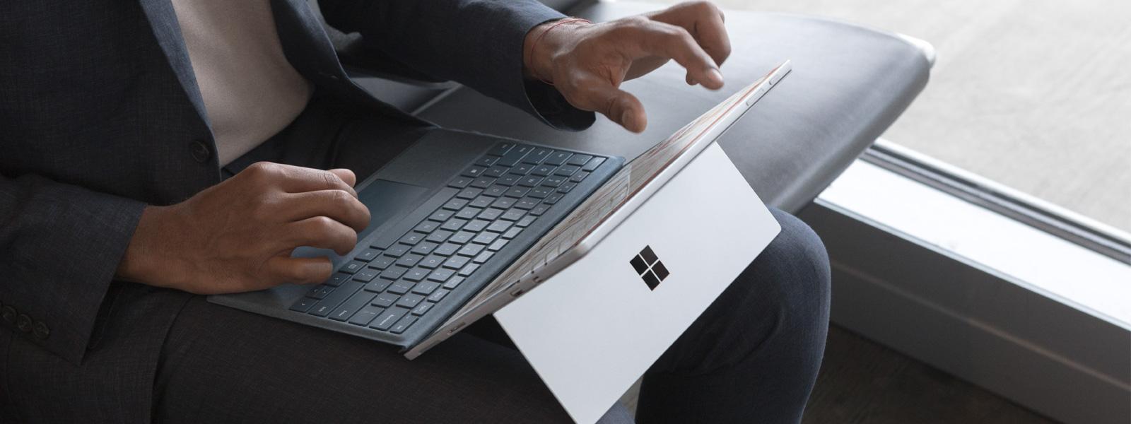 兩個女人在咖啡廳使用鍵盤反折的 Surface Book 2。