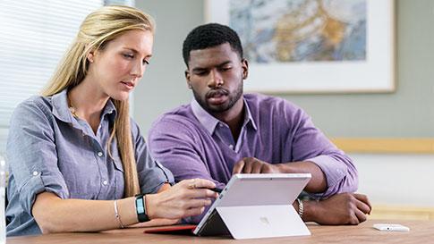 女人和男人坐在桌前,使用 Surface Pro 4 的觸控螢幕。