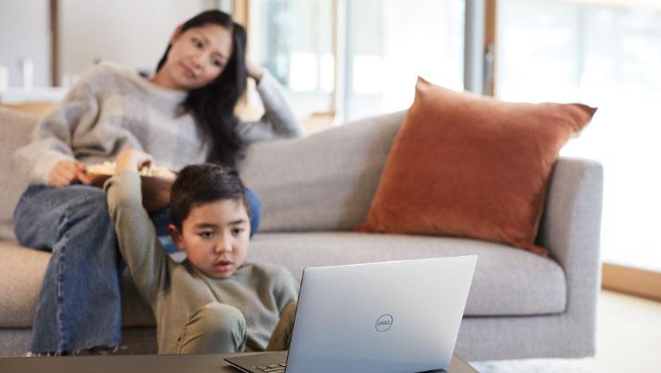 女人和小孩一邊吃爆米花,一邊看著 Windows 筆記型電腦