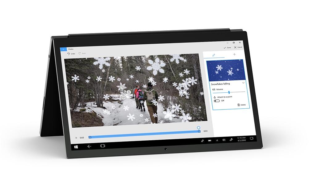立著的筆記型電腦顯示相片應用程式,以及背包客在森林裡健行的影像,影像覆蓋著 3D 雪花效果